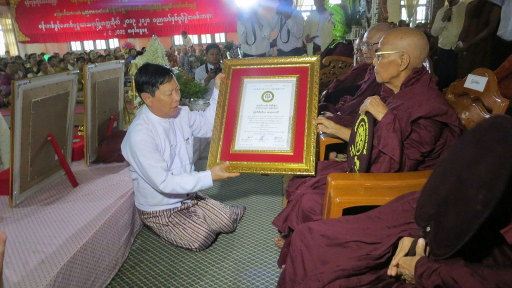 Union Minister Thura U Aung Ko presents the certificate to the Ovadacariya Sayadaw of Pan Tapwint Taung Buddhist Missionary University yesterday.Photo: MNA