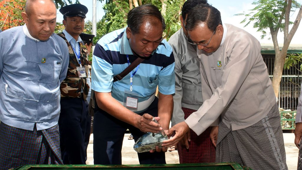 Union Minister U Ohn Win observes the quality of the jade stones at the Myanmar Gems Emporium in Nay Pyi Taw yesterday.Photo : MNA