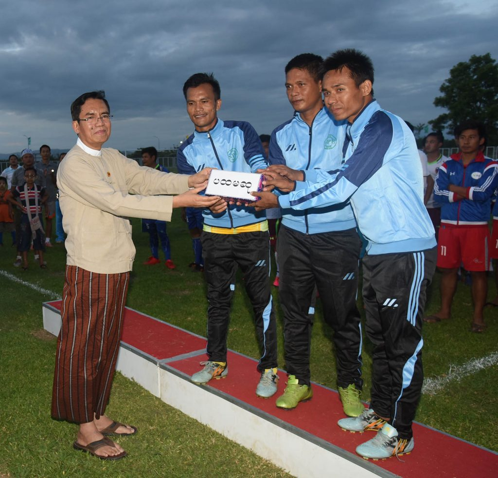 Deputy Minister U Aung Hla Tun awards the first prize to the News and Periodicals Enterprise team.  Photo : mna
