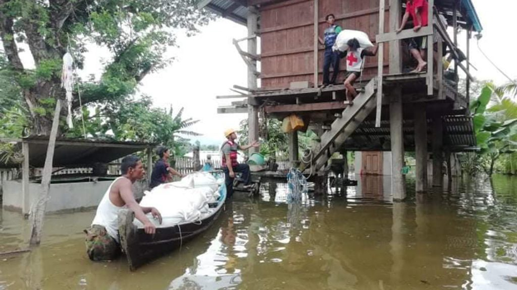 Myanmar Red Cross members carrying aids using a boat to help residents affected by flood in Sinbo.Photo: Kachin State IPRD