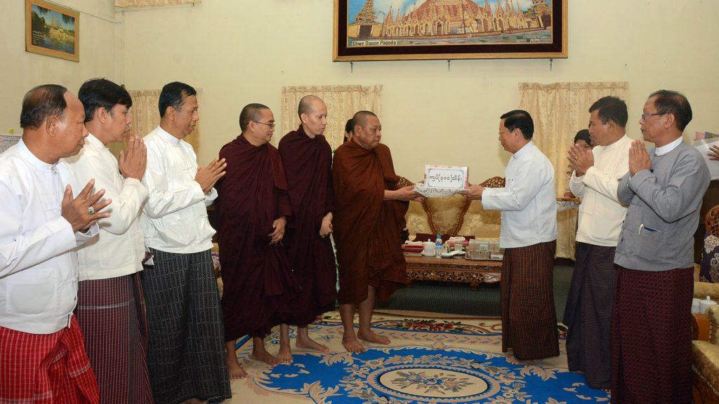 Union Minister Thura U Aung Ko accepts the cash donated by Sayadaw Bhaddanta Virira for Eternal Peace Pagoda. Photo : mna
