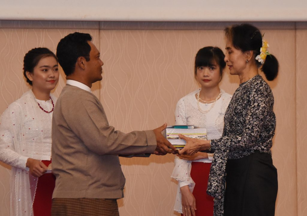 State Counsellor Daw Aung San Suu Kyi presents stationaries to a staff at the ceremony in Nay Pyi Taw. Photo: MNA