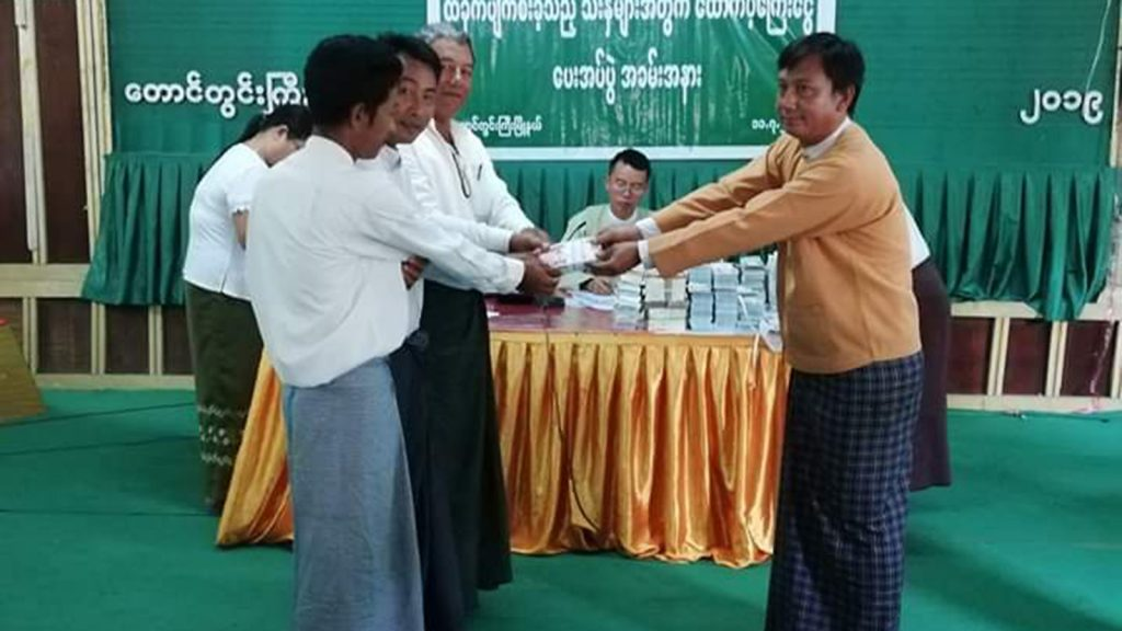 An offical of Taungdwingyi Township provides cash assistance to farmers  affected by flooding in Taungdwingyi, Magway Region.  Photo: Naing Win