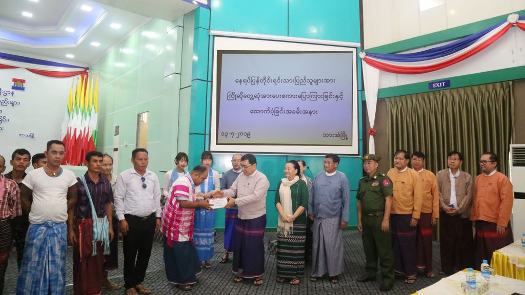 Union Minister Dr Win Myat Aye presents cash to local people in Hpa-an Township, Kayin State yesterday. Photo: MNA