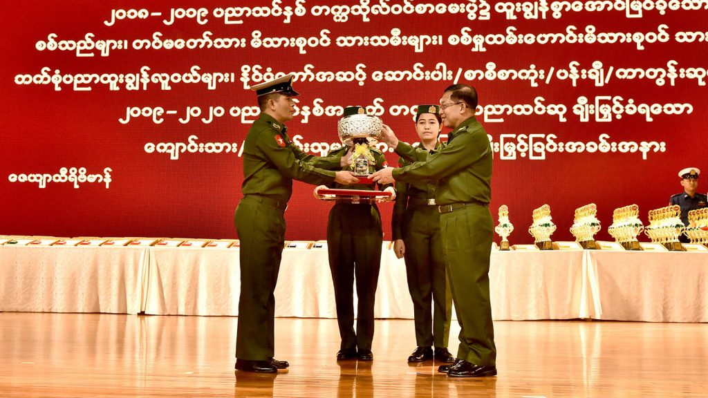 Senior General Min Aung Hlaing presents a prize to an in-charge officer of a school management for achieving highest pass rate in 2018-2019 academic year at the ceremony to honour outstanding servicemen, offspring of servicemen and war veterans.Photo: Office of the C-IN-C of Defence Services