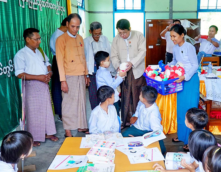 Union Minister Dr Pe Myint presents the gift to the child at Taungdwingyi Township's Information and Public Relations Department Office yesterday.Photo: MNA