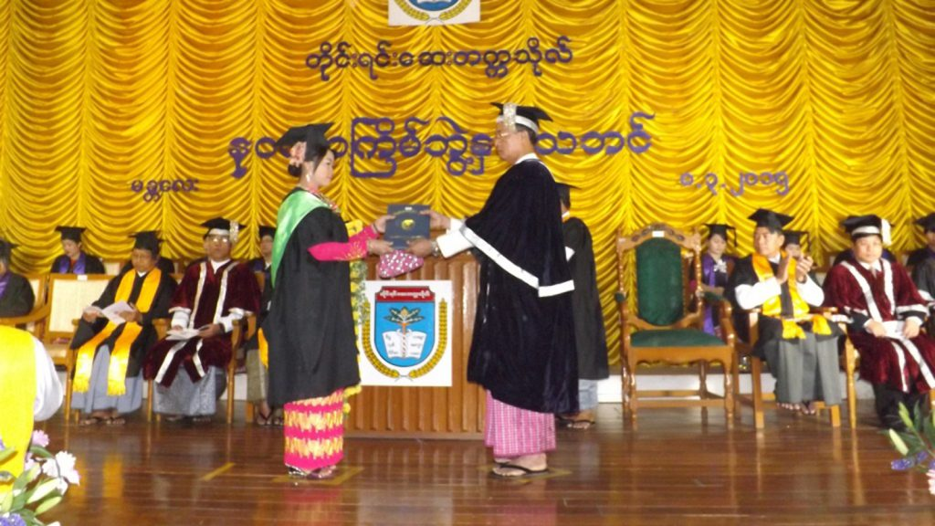 A student receives academic degree from the Mandalay University of Traditional Medicine during convocation.