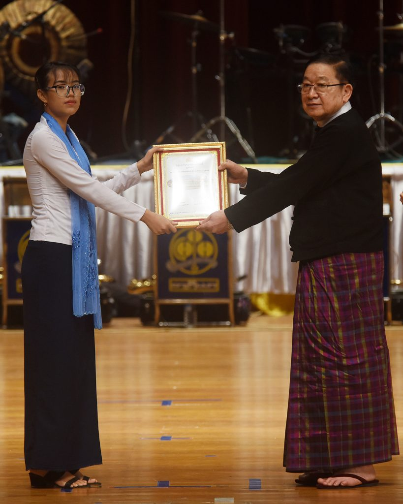 Pyidaungsu Hluttaw Speaker U T Khun Myat presents the third prize of the university-level essay contest to a student.  Photo: MNA