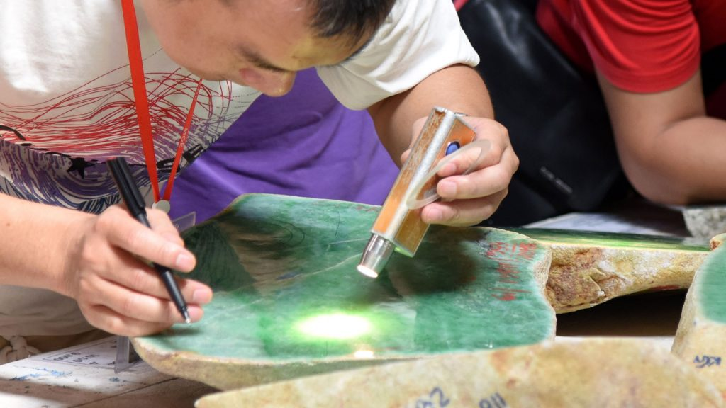 A man evaluates the jade lot on 6th day of mid-year Myanmar Gem emporium. Photo: Aye Than