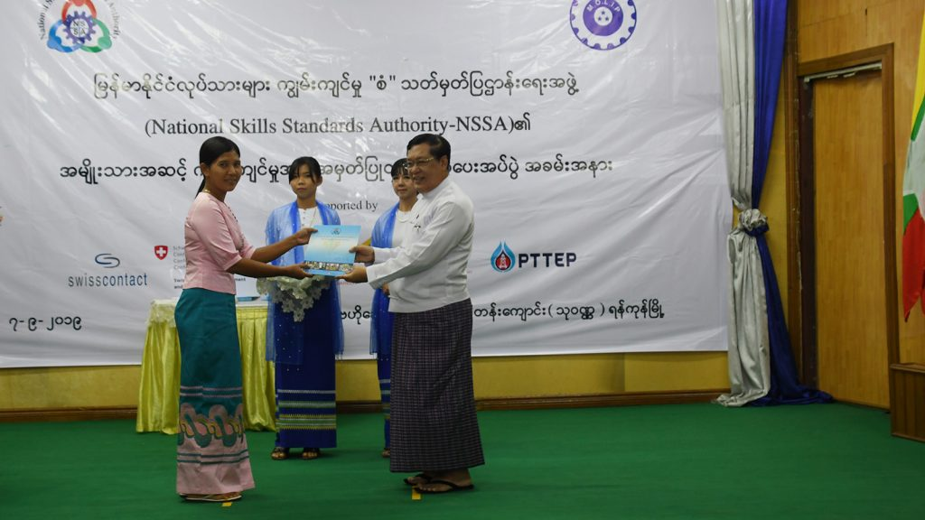 Union Minister U Thein Swe presents the certificate of recognition to a trainee at the National Skills Standards Authority certificate awarding event in Yangon yesterday.Photo:MNA