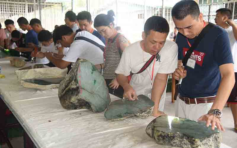 Jade merchants check quality of a jade stone during the mid-year Myanmar Gem Emporium at Maniyadana Jade Hall in Nay Pyi Taw on 21 September.Photo: Min Min Zaw (kalay)