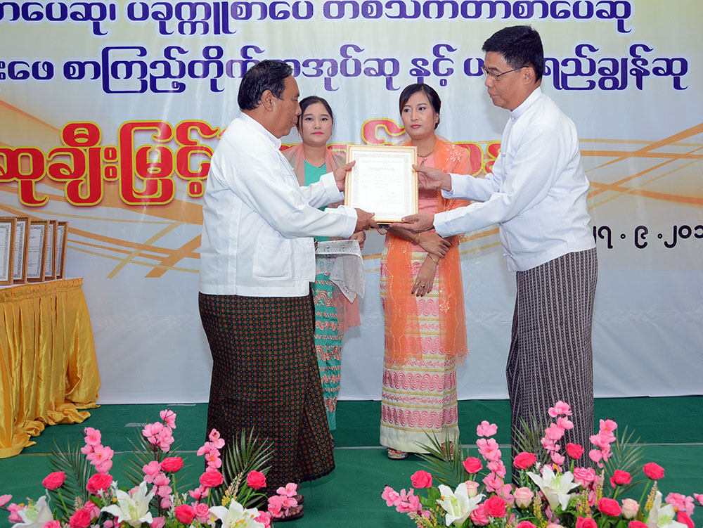 Director-General U Aung Myo Myint presents an award to Chit Su Aung for winning first place at the 2018 poem contest in Yangon. Photo: MNA
