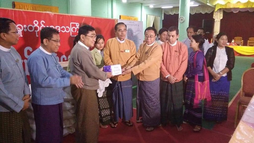 Union Minister Dr Win Myat Aye hands over cash assistance for flood victims in Bago Region.Photo: MNA