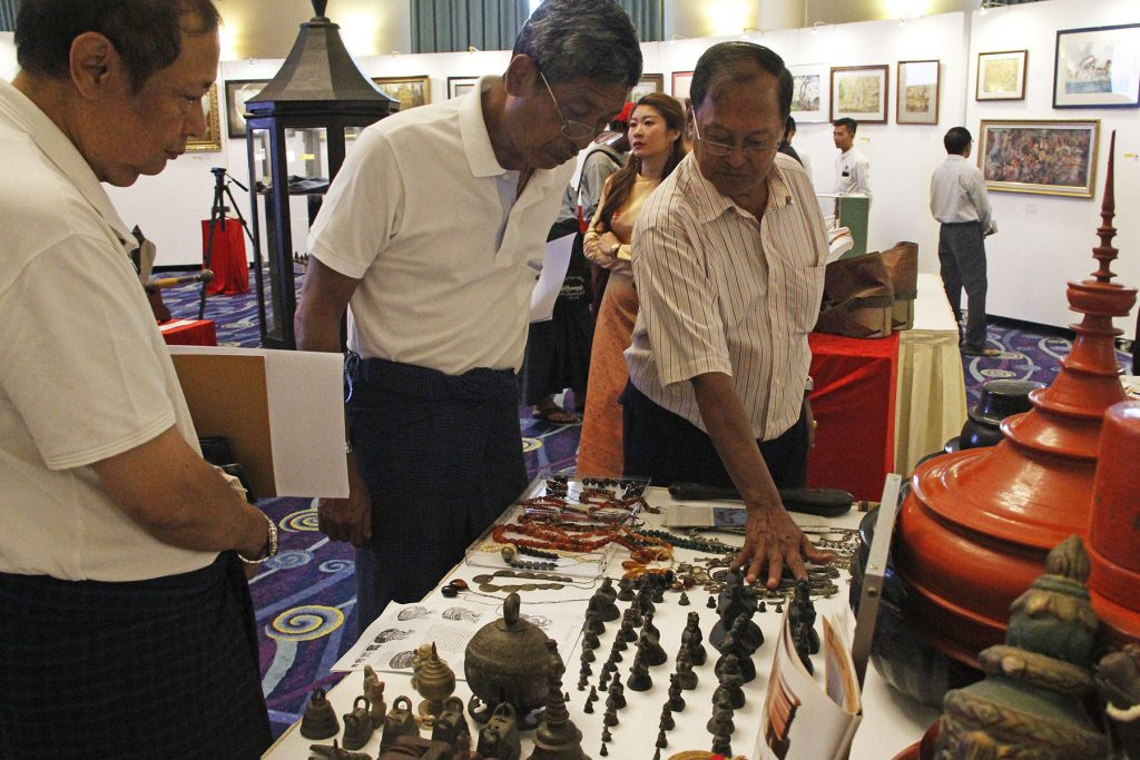 Visitors observe art works displayed by Myanmar artists  at the Inya Lake Hotel in Yangon on 21 September.  Photo: gnlm