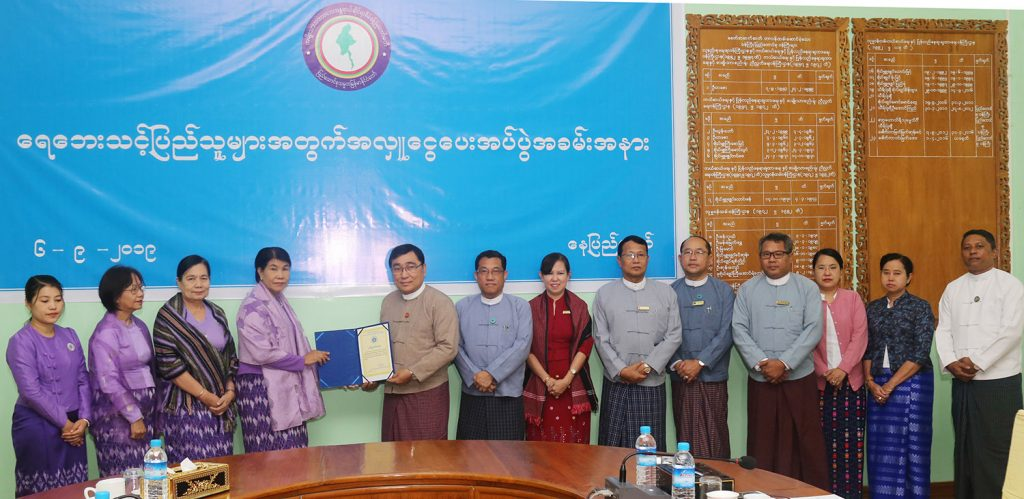 Union Minister Dr Win Myat Aye presents the certificate of appreciation to the official from Myanmar Maternal and Child Welfare Association for their donation for rehabilitation in flooded area.Photo: MNa
