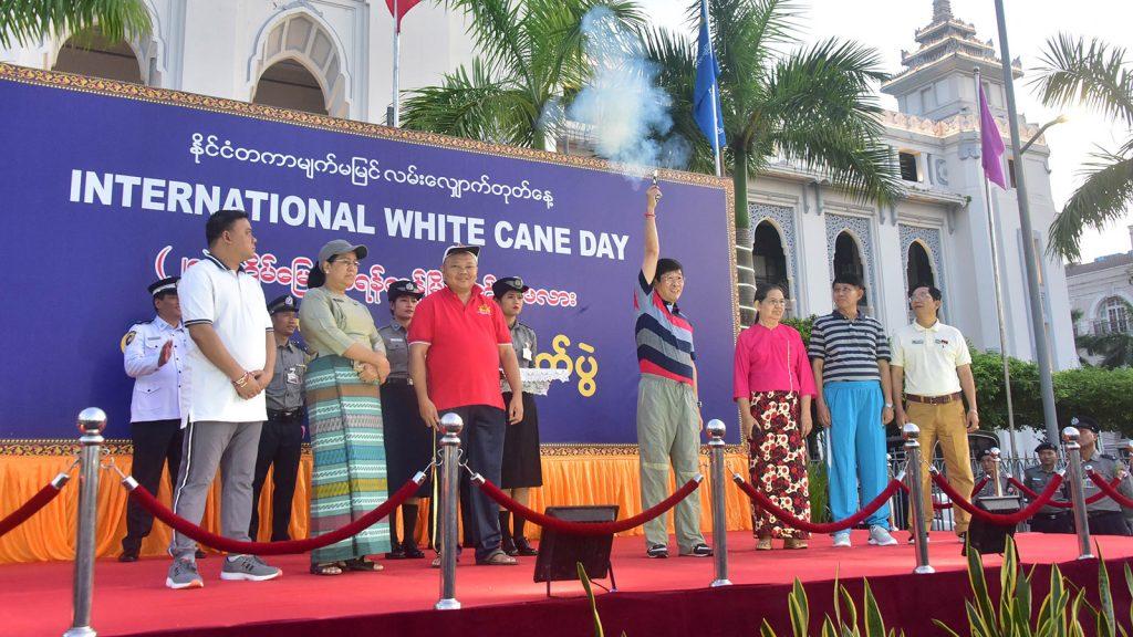 Deputy Mayor of YCDC U Soe Lwin shots up the starter's gun to start the 28th International White Cane Day walk yesterday.Photo: Zaw Min Latt