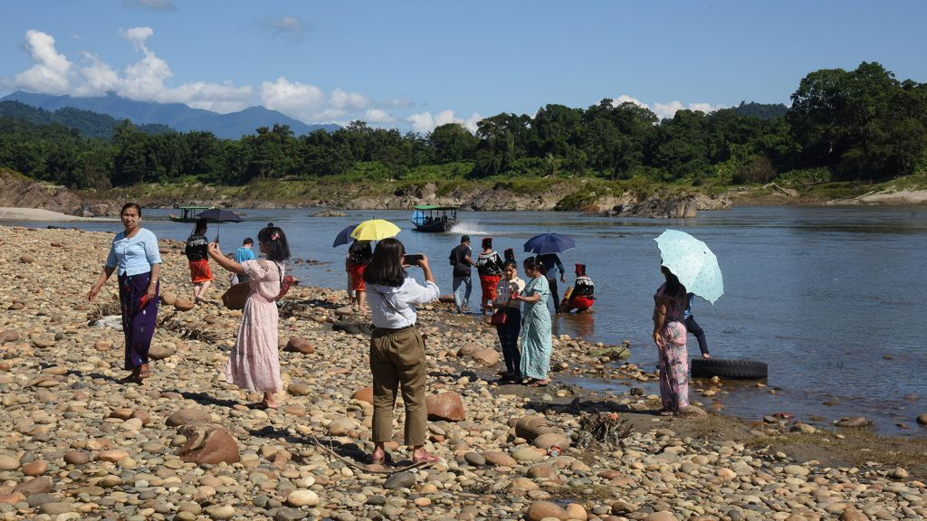 Visitors taking photos along the riverbank at the Myitsone in Kachin State.Photo: Htein Nan Naw