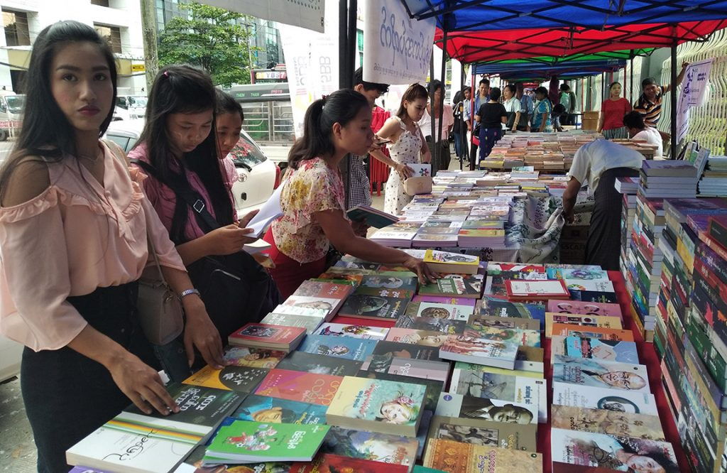 Book lovers select books at the the Yangon Weekend Book Street yesterday.Photo: Thant Zin Win