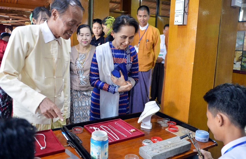 State Counsellor Daw Aung San Suu Kyi observes making  jewelleries at Sein Thamadi Gold and Silver Smith Industry in Heya Ywama Village, Shan State yesterday.Photo: Thet Aung