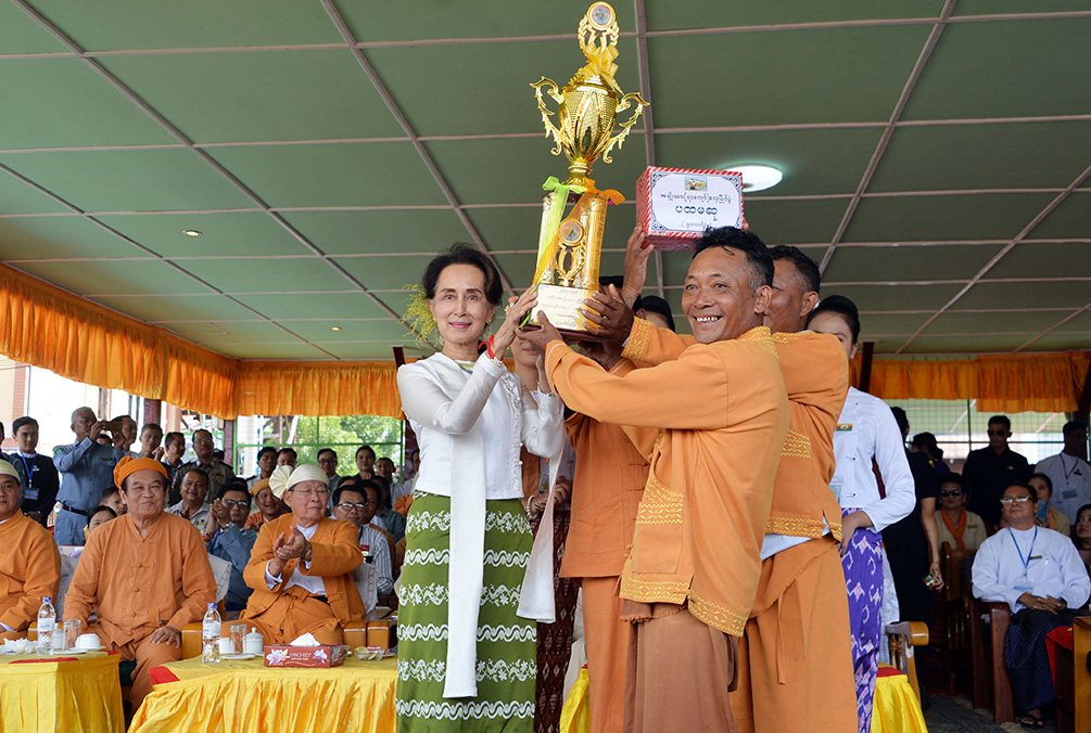 State Counsellor Daw Aung San Suu Kyi presents the trophy to the first prize winning team of the Inntha traditional boat race, Kay La Sate Ta village team.  Photo: Thet Aung