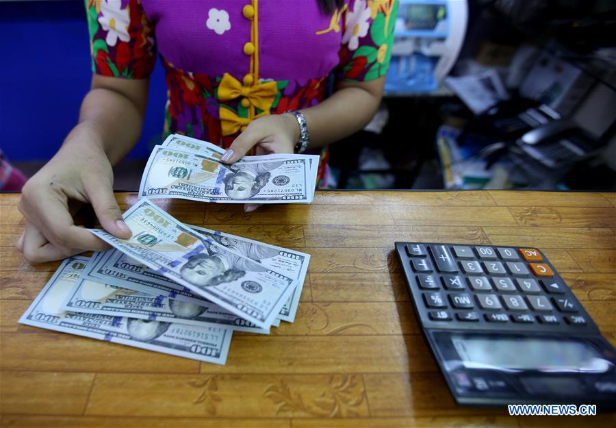 A clerk checks U.S. hundred dollars bills at a foreign currency exchange counter in Yangon. Photo Xinhua