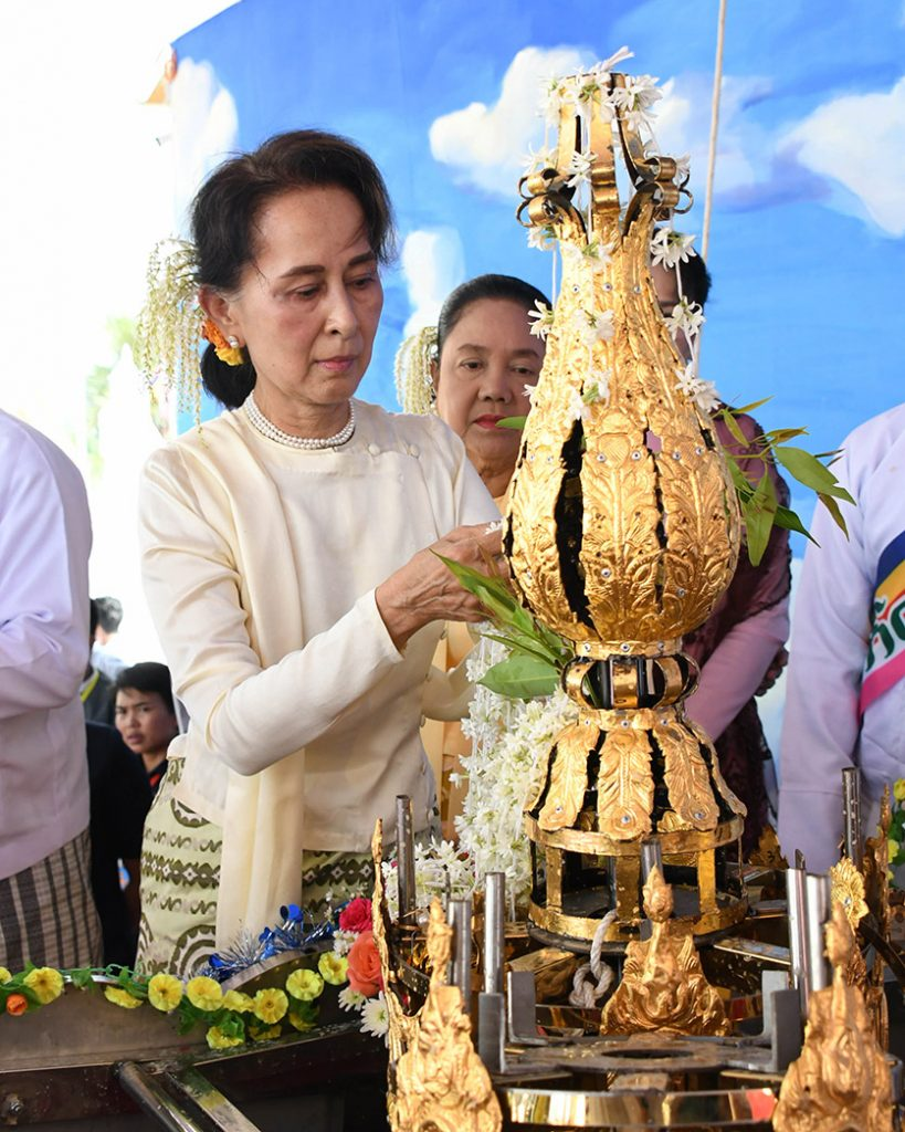 State Counsellor Daw Aung San Suu Kyi sprinkles scented water over the religious object before it is fixed atop the Eternal Peace Pagoda. Photo: MNA