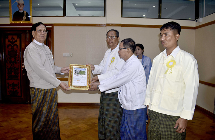 Amyotha Hluttaw Deputy Speaker U Aye Tha Aung accepts the certificate of honour for donation from Yin Yoe pagoda's board of trustee in Rakhine State.Photo: MNA