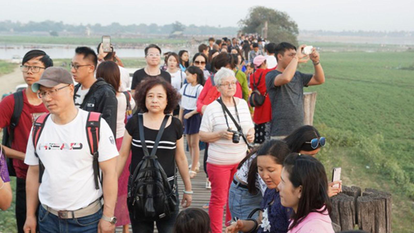 Travellers walk on U Bein Bridge over Taungthaman Lake in Mandalay.Photo: Than Zaw Min (IPRD)