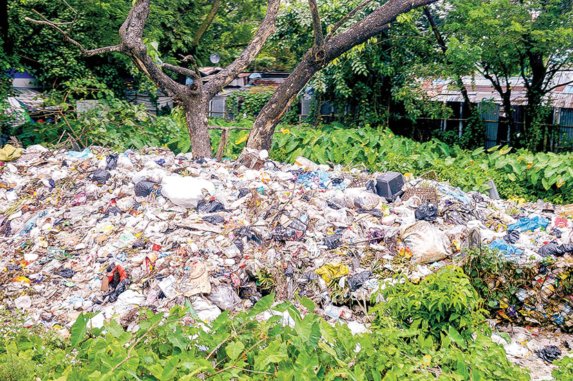 A pile of plastic garbage dumped in an open dump in a town.