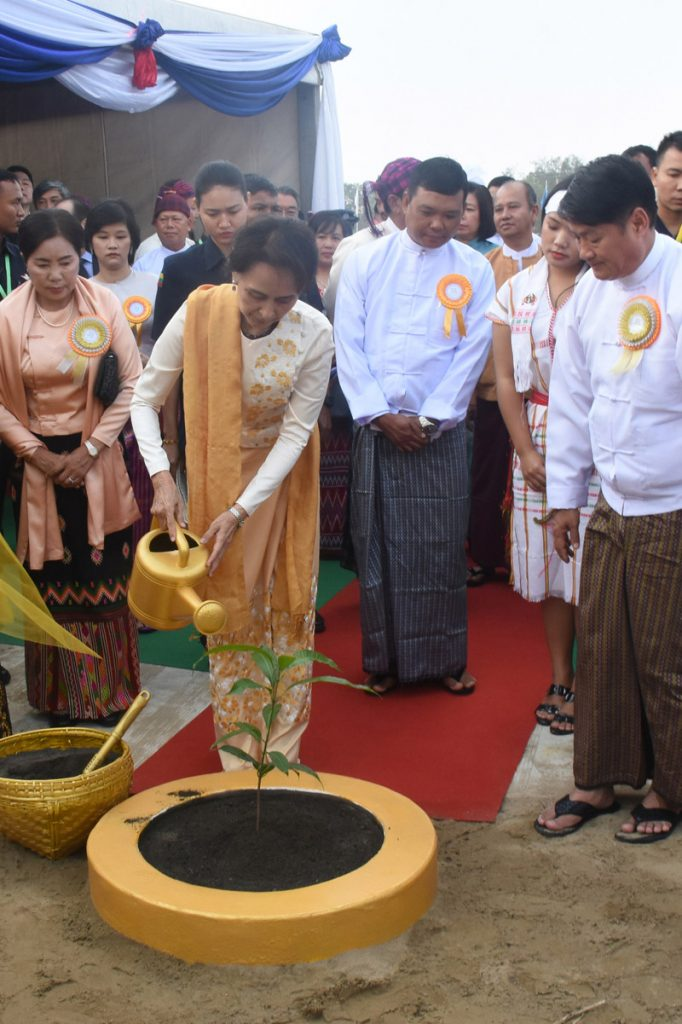 State Counsellor Daw Aung San Suu Kyi pouring water on a mango tree at the stake driving ceremony of the Shin Rai International Vocational Institute in Yangon yesterday.Photo:MNA