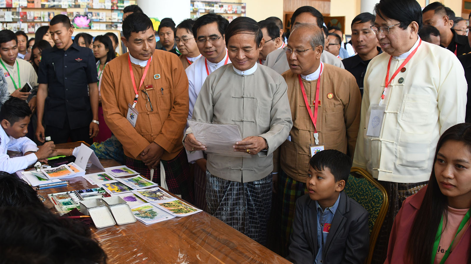 President U Win Myint looks at the drawing and painting created by students at the Youth All-Round Development Festival at Magway University in Magway Photo:MNA