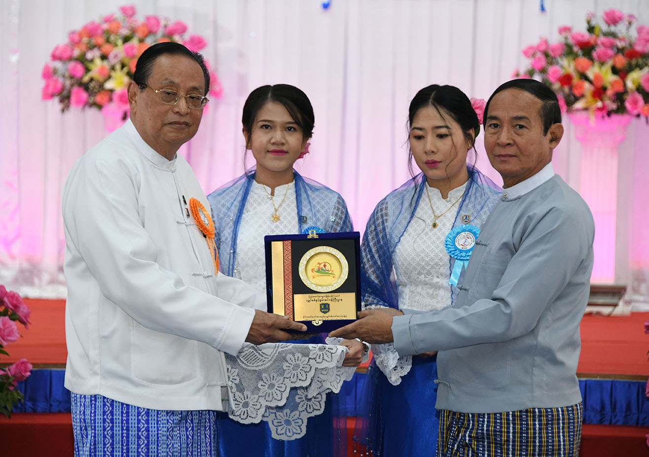 President U Win Myint accepts a gift commemorating the event for the achievement of 50% nationwide electrification from Union Minister U Win Khaing in Nay Pyi Taw. Photo: MNA