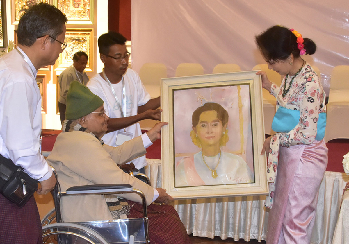State Counsellor receives her portrait painting by U Lun Gywe at the 'Hay Manda Art Exhibition' at the Strand Hotel in Yangon yesterday. Photo: MNA
