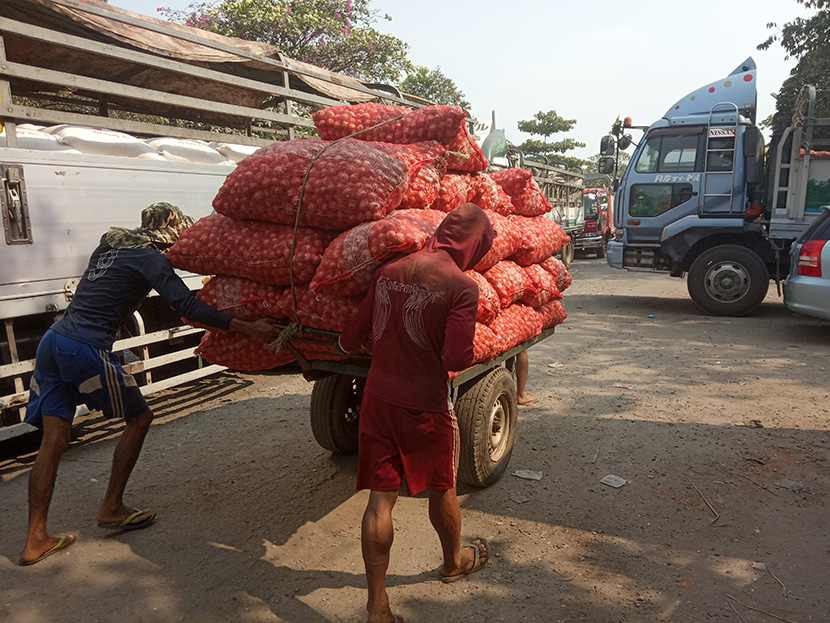 Workers carrying sacks of onion towards the truck parked near a warehouse in Yangon. Photo: supplied