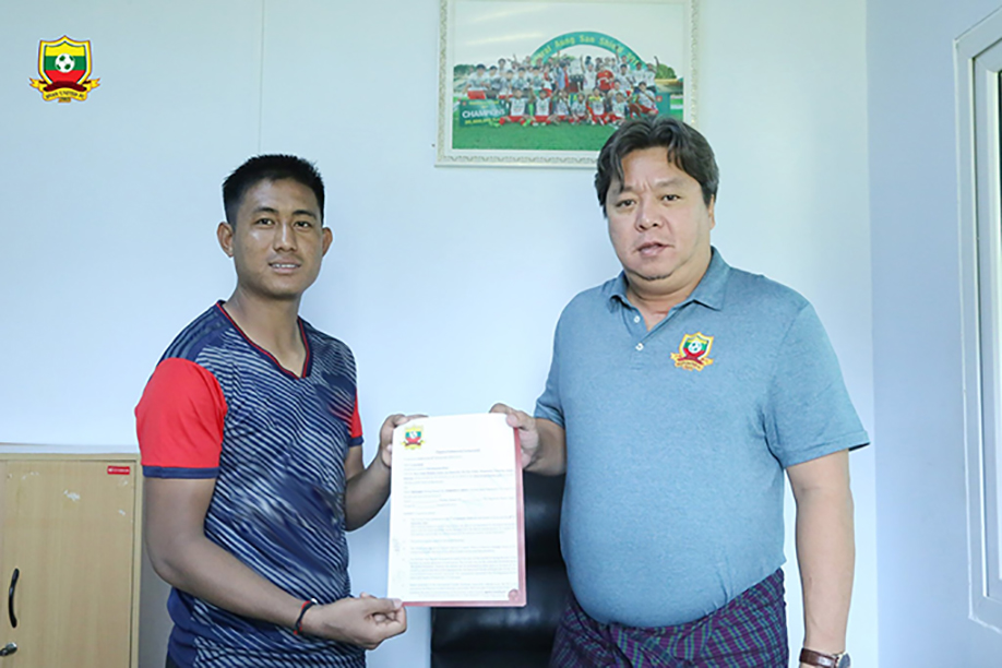Defender Nyein Chan (L) receives his contract with Shan United. photo: sufc