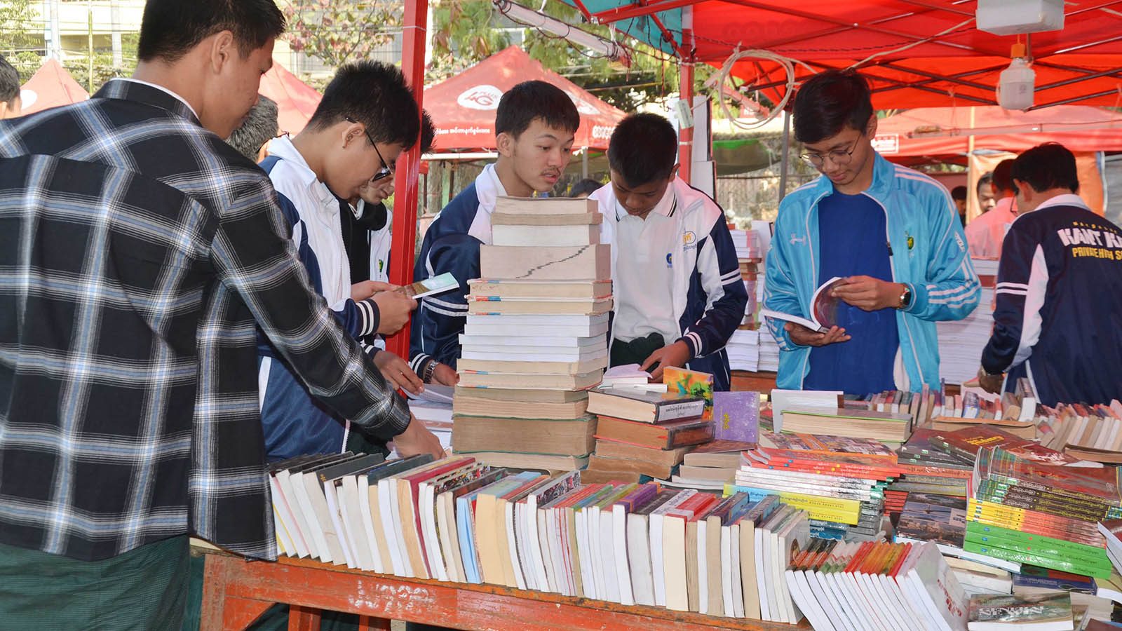 School children browse books displayed at the centenary celebration of Nandawshae Reading Association. Photo: Aung Phyo Kyaw