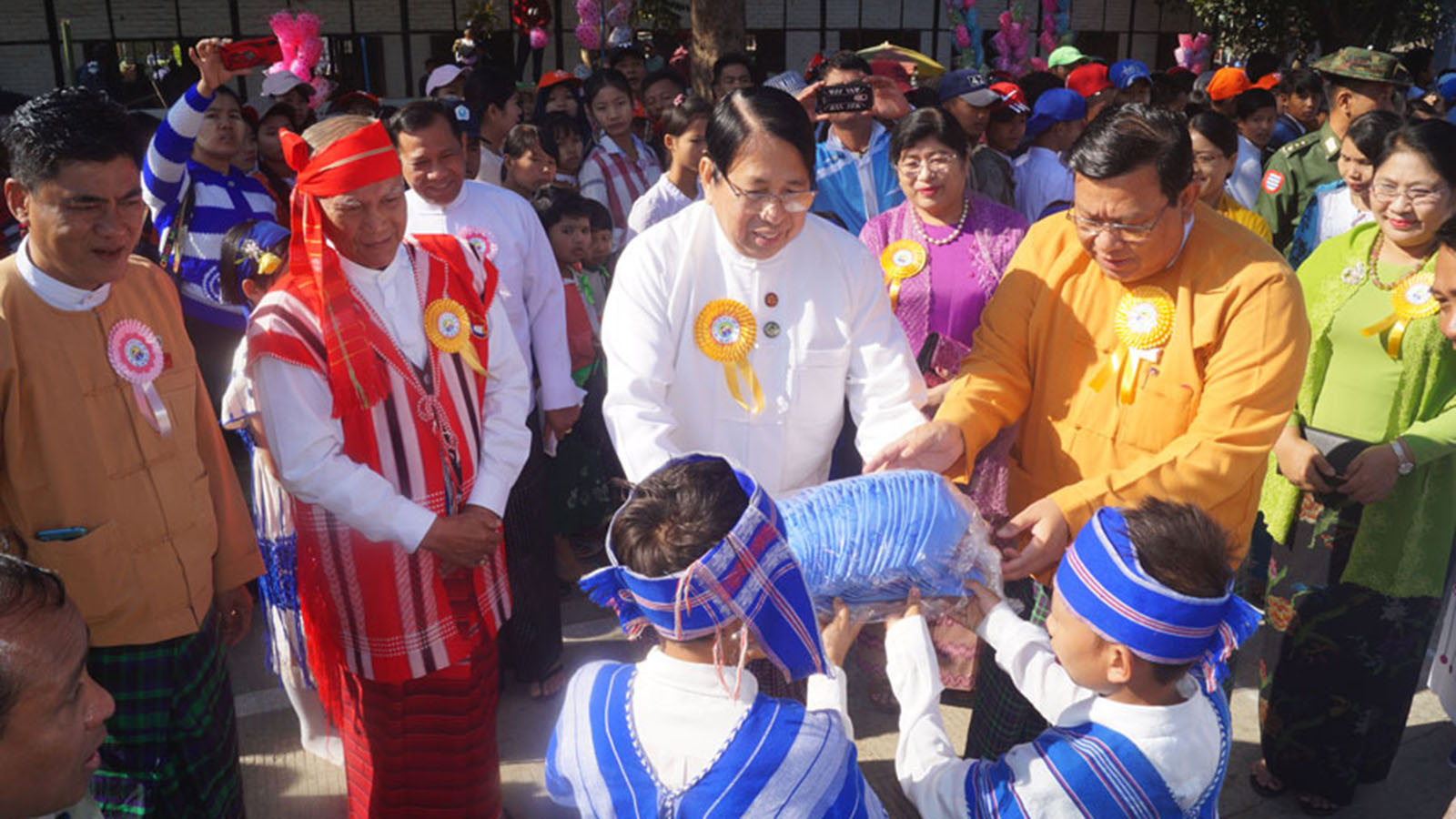 Union Minister Dr Pe Myint and Ayeyawady Region Chief Minister U Hla Moe Aung present shirts to students at the Children Literary Festival in Kyonpyaw, Ayeyawady Region yesterday.Photo: Soe Min Oo (IPRD)