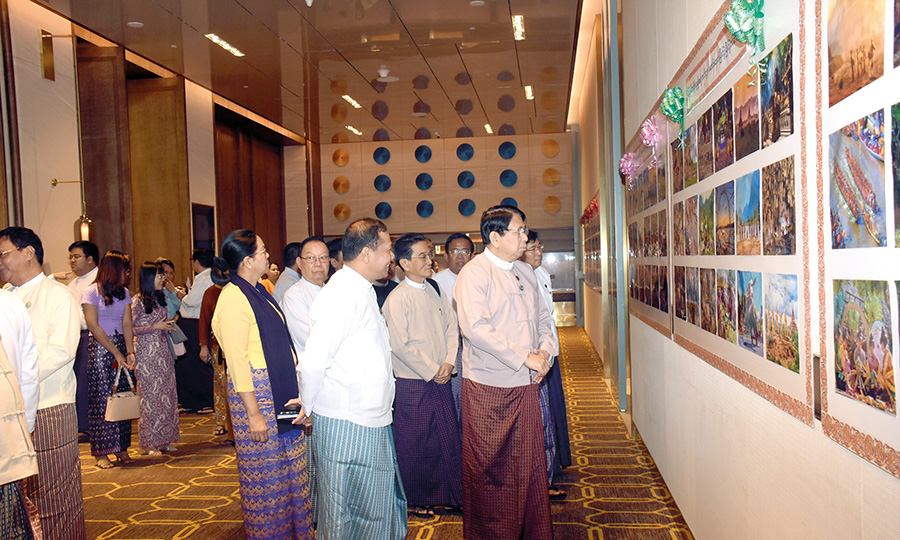 "Union Minister for Information Dr Pe Myint looks winners' photos displayed at the photo and postcard contests organized by the Information and Public Relations Department under the title of ""Value of State, Prestige of Nationality"" in Yangon yesterday. Photo: MNA"