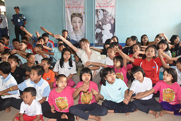 Chinese actress Qiao Xin dances with the children from Andrew Youth Orphanage in Gontalapaung Village, Mingaladon Township, yesterday.  PHOTO:  Zaw Min Latt