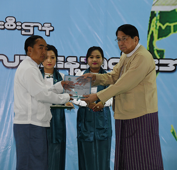 Union Minister Dr Pe Myint presents the third prize for performance award to Haka District IPRD Office at the ceremony.Photo: MNA