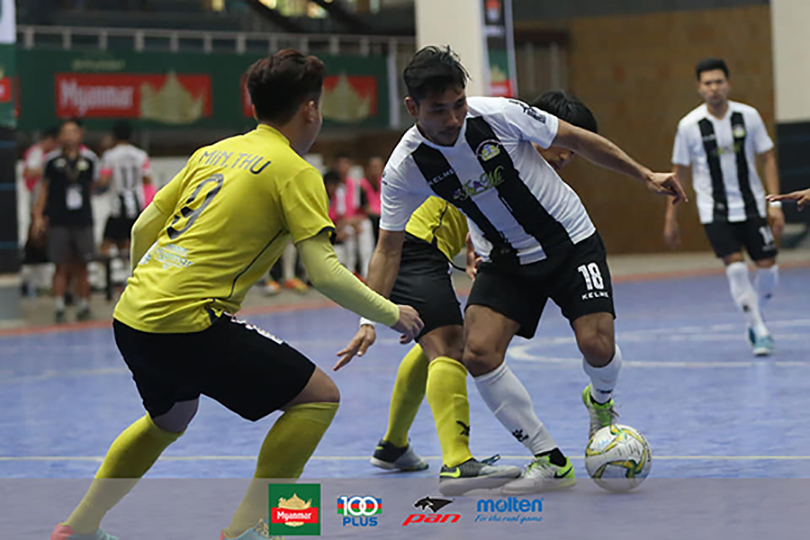A VUC FC player (white and black) vies for the ball with On Doctor FC players (yellow) during the Week-15 match of the Myanmar Futsal League held yesterday at the National Indoor Stadium II in Yangon. Photo: MFF Futsal