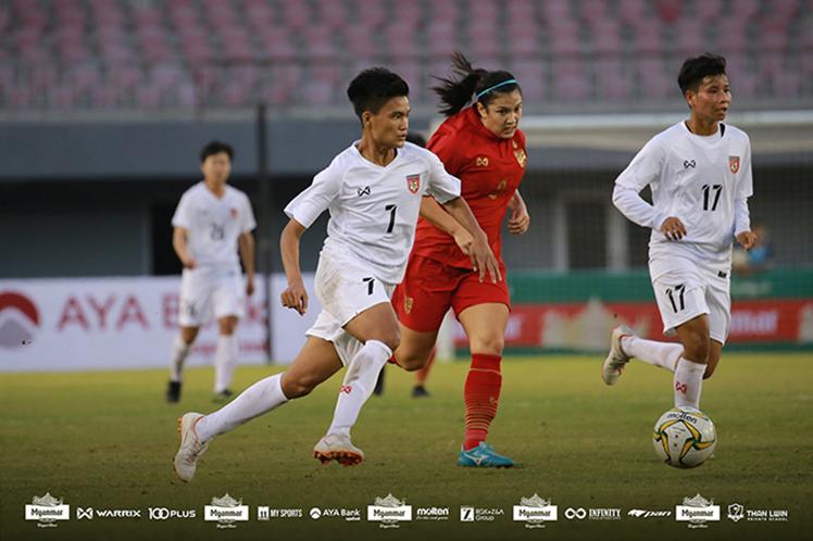 Myanmar's Win Theingi Tun (No 7) carries the ball during yesterday's friendly match with Thailand at Mandalar Thiri Stadium in Mandalay. Photo: MFF