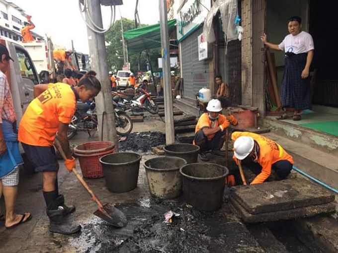 YCDC workers cleaning garbage systematically in front of the buildings. Photo: Phe Zaw
