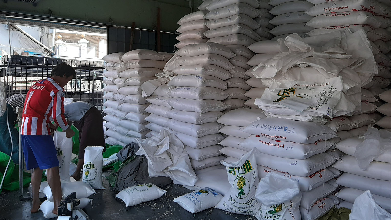 Workers packaging sacks of rice at a warehouse in Yangon. photo: Tin Zar Hlaing