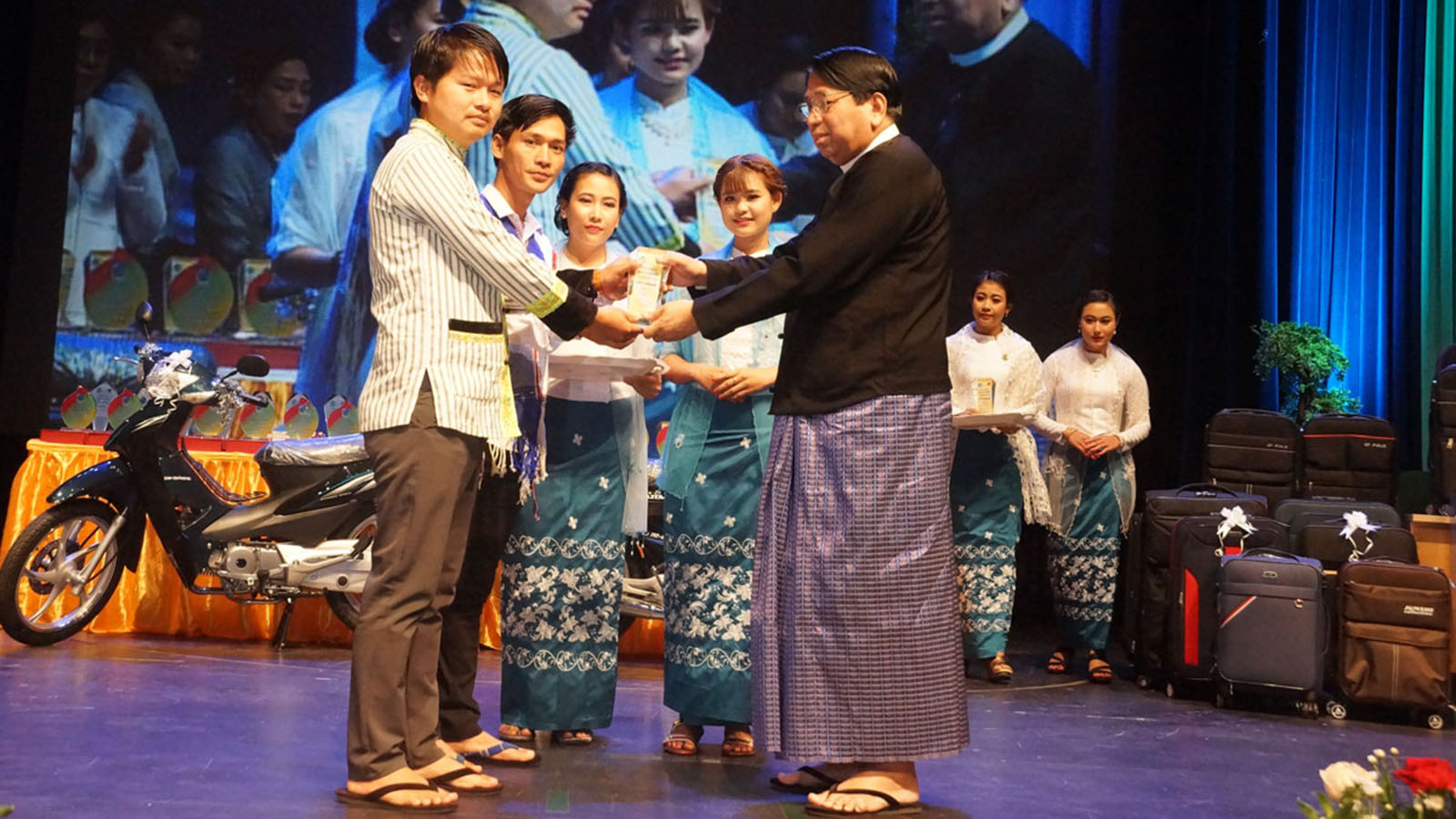 Union Minister Dr Pe Myint presents the award to the staff of the National Races Channel for their efforts in travelling to remote Khaunglanphu area in Kachin State.Photo: MNA