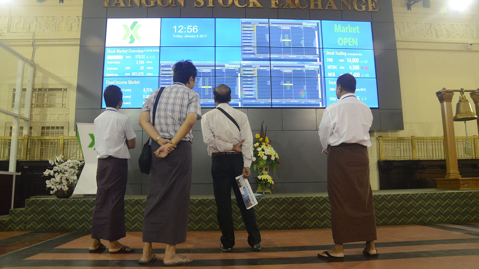 People look at the electronic board showing the stock exchange rate in Yangon Stock Exchange. Photo: Phoe Khwar