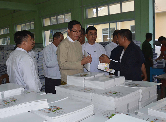 Deputy Minister for Information U Aung Hla Tun observes the school text books at the printing house in Mandalay yesterday.Photo: MNA
