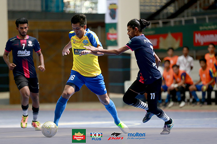 MIU FC player (yellow) attempts to block the ball from GV FC player (black) during Week-20 of the Myanmar Futsal League match at National Indoor Stadium II in Yangon yesterday. Photo: MFF Futsal