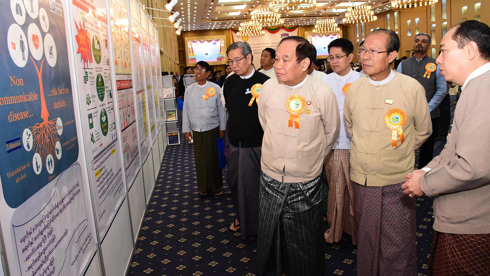 Union Minister Dr Myint Htwe and Nay Pyi Taw Council Chairman Dr Myo Aung look around the posters displayed on the exhibition hall during the ceremony in Nay Pyi Taw yesterday. Photo: MNA