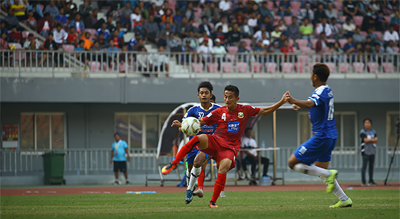 Shan United's David Htan (red) torches the ball during the Myanmar National League match against Yadanarbon F.C. yesterday at the Mandalar Thiri Stadium in Mandalay. Photo: MNl